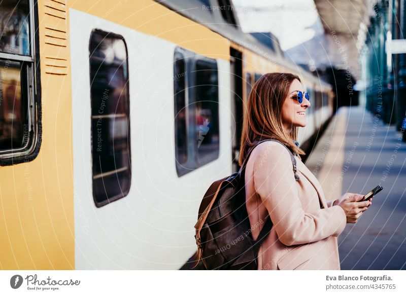 happy backpacker caucasian woman at platform on train station using mobile phone. Travel concept travel technology daytime Porto arrival baggage beautiful board
