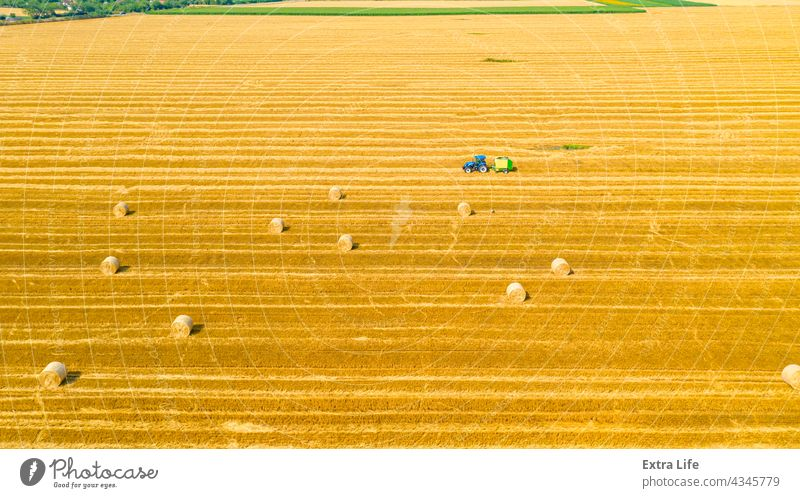 Aerial view of tractor tow trailed bale machine to collect straw from harvested field Above Agricultural Agriculture Arable Bale Baler Baling Cereal Compact