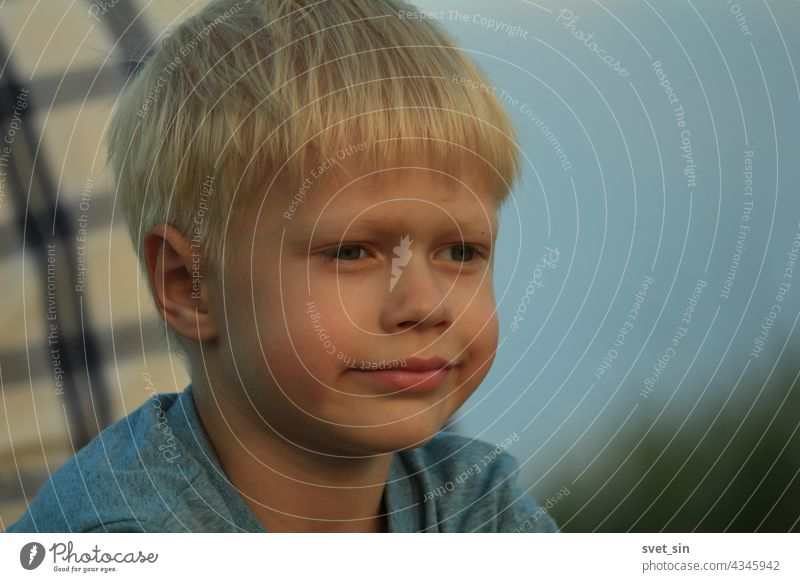 Portrait of a pensive blond boy against the background of a man's back in a plaid shirt and blue sky on a summer evening outdoors. blonde kid portrait child