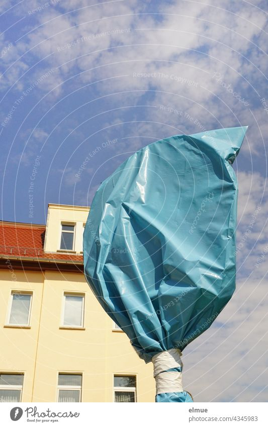 traffic sign covered with a blue plastic bag in front of an apartment house in the sunshine with deco clouds / construction site / invalid traffic sign