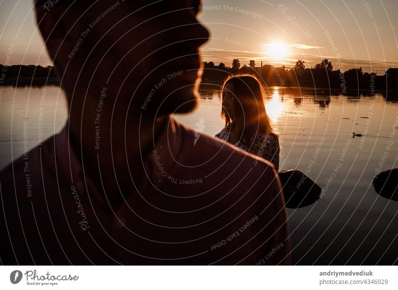 silhouette of couple in love near the lake on sunset. Lovely happy couple having fun near outdoors. happy holiday concept. selective focus young people romantic
