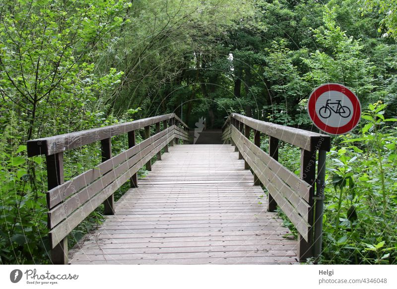 No bicycles! - Wooden bridge in the park with prohibition sign for cyclists Bridge Road sign interdiction Prohibition sign Ban for cyclists Tree shrub Park