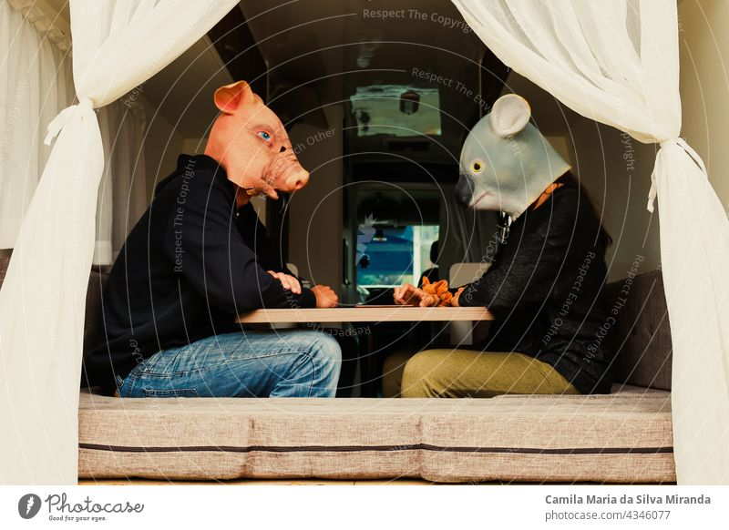 Couple with animals sitting at the table in a motorhome. Traveling couple. adventure animals mask auto home camper car driving freedom happy holiday house koala