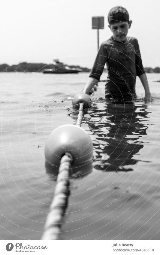 Young boy holding onto rope barrier at lake; buoys on rope wade safety pre-teen autism special needs isolated solitary beach summer water nature vacation