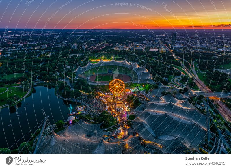 Beautiful Munich sunset from a bird's eye view with a festival in the popular Olympiapark and the stadium in the bright orange twilight. people Festival Above