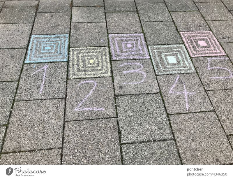 1,2,3,4,5 is written on the floor with sidewalk chalk. Box hopping, children's game, hopping game. street chalk Infancy square hopping Hop Children's game Joy