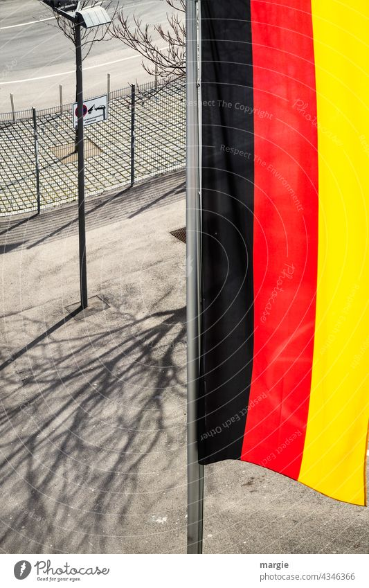 View from above on a vertical Germany flag Flag Blow Exterior shot Judder Deserted Flagpole Fence Street lighting Shadow Colour photo Beautiful weather