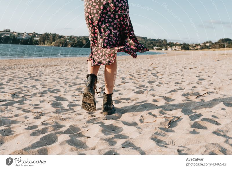 Back shot of a woman walking on the beach during a sunny day with a skirt, copy space, summer concept sand carefree carrying erotic fitness freedom glamour