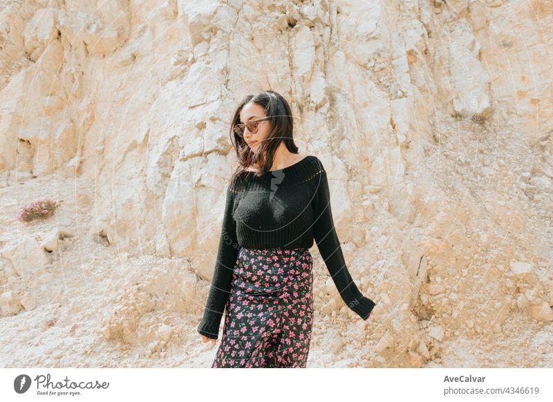 Portrait of a young woman with a pair of sunglasses in front of a marble giant rock, liberty and freedom concept lady smile person pretty enjoy model camera