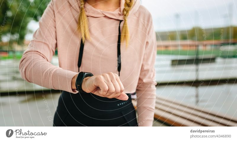 Young sportswoman looking activity bracelet unrecognizable athlete smartwatch midsection copy space pedometer training morning fitness active attractive