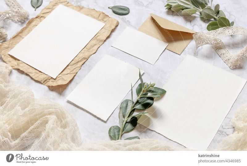 Wedding blank cards laying on a marble table decorated with eucalyptus branches mockup invitation envelope rustic close up ribbons retro RSVP vintage kraft