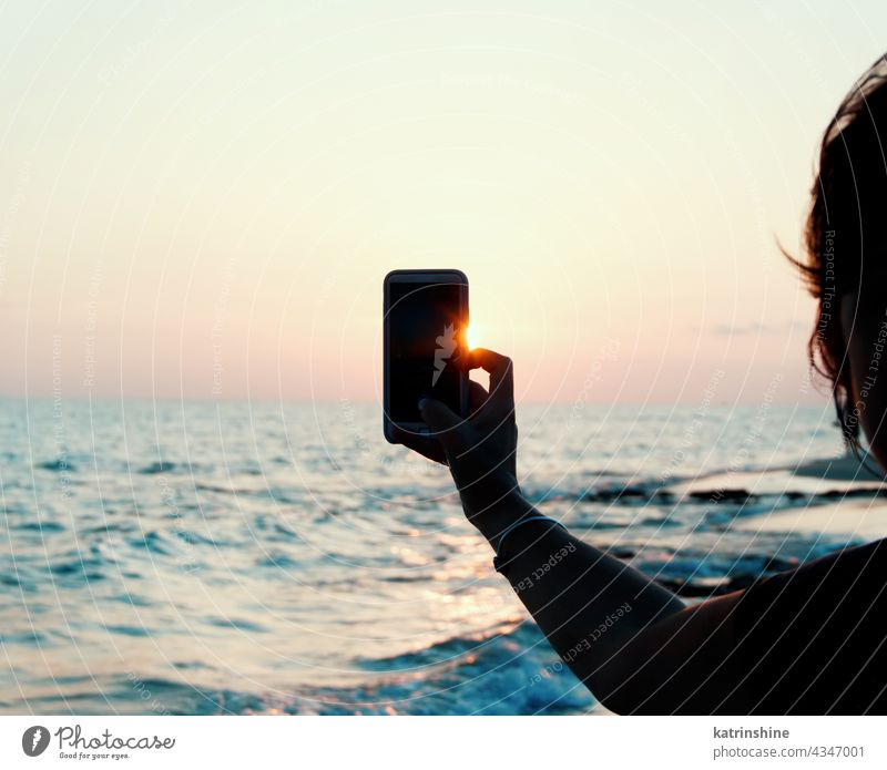 Woman takes a sunset photo on the mobile phone hand close up taking photo beach sea Landscapeб Mobile mobile blue Holding Faceless copy space Sky Communication