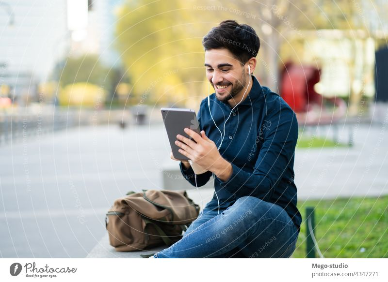 Young man having a video call on digital tablet outdoors. young technology mobile working social network touchscreen outside online concept display wireless