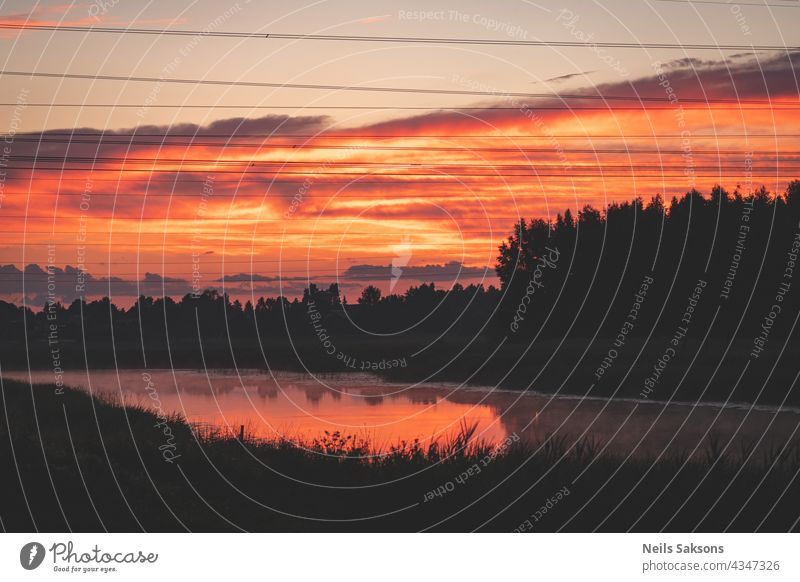 sunset over the river. Red orange clouds. Black forest silhouette over the river. Electric power line wires in he air. Reflection of clouds and reeds in river makes it orange