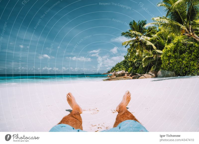 man resting on the white sand beach with beautiful palm trees seychelles travel vacation tropical sun summer relaxation outdoor ocean leg island coast tourism