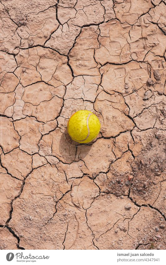 yellow tennis ball on the dessert ground sport object still life brown old abandoned land dry textured earth nature desert climate pattern dirt arid sand