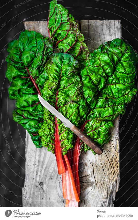 Fresh raw chard leaves and a knife on a wooden cutting board Mangold Raw Knives Rustic Chopping board Wood Vegetable Vegetarian diet Ingredients Green Healthy
