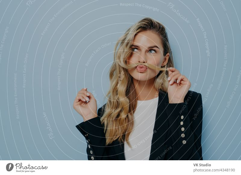 Funny joyful blonde woman having fun while posing against blue studio wall, playing with strand of hair funny carefree happy beautiful young white pretty