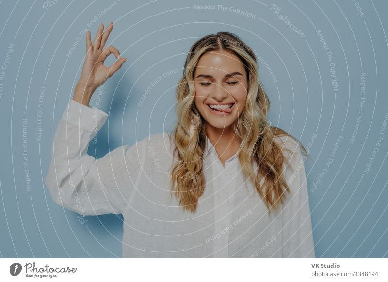 Crazy blonde woman making ok gesture while showing tongue crazy funny young okay silly facial expression closed eyes joyful cheerful face isolated lady lips