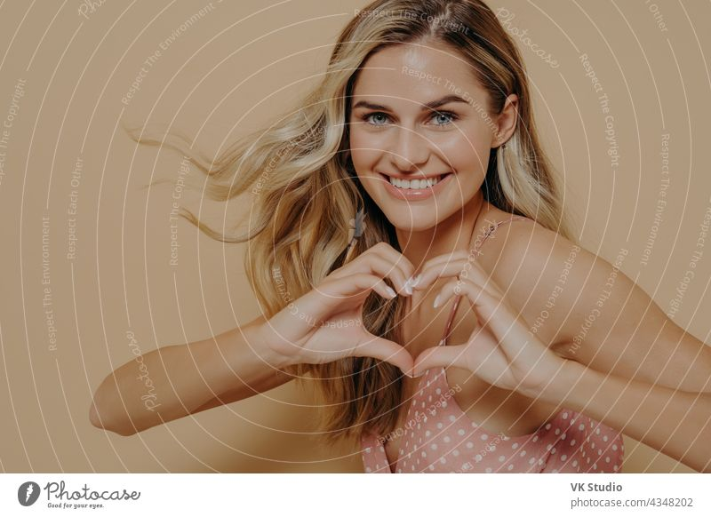 Blonde woman making heart shape with her hands upbeat blonde showing gesture love smile smiling displaying affection tender happy face isolated expression joy