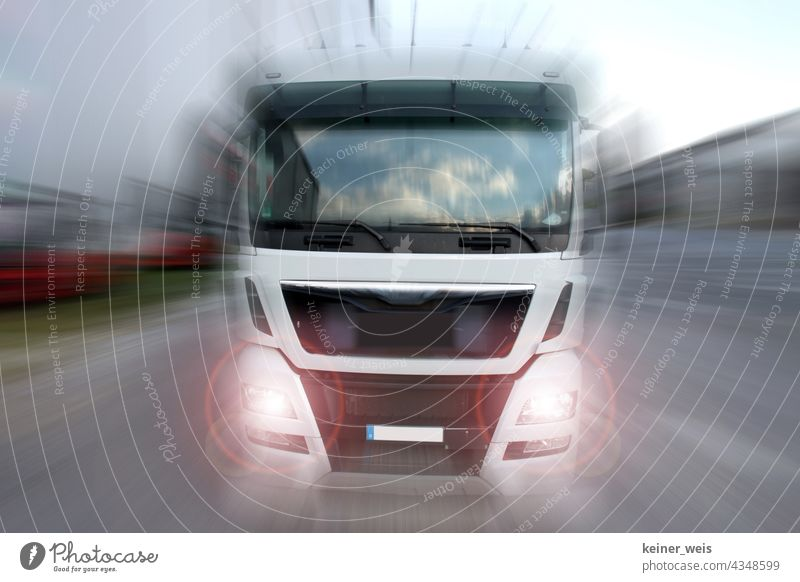 A truck drives towards the viewer with blinding headlights Truck lorry lorries Logistics Transport logistics Shipping Vehicle Delivery cargo Street Industry