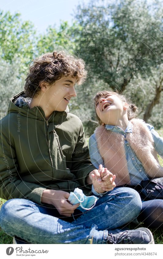 Two young siblings, a boy and a girl, sitting on the grass in a park holding hands, laughing together. With masks held in the hand of one of them. An out of focus background of trees. Post-vaccination concept
