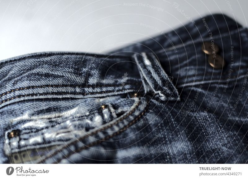 Almost new, cult and stylish: detail shot of a pair of washed out and torn blue jeans with trouser pocket, belt loop and metal buttons Bluejeans style Fashion