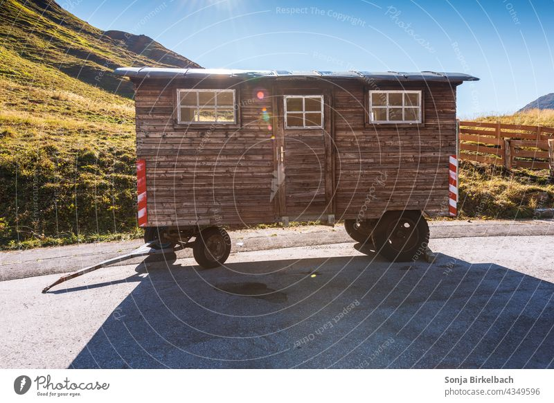 Wooden construction trailer parked in the mountains Site trailer Carriage Trailer Colour photo Exterior shot Caravan Old Nature Day Deserted Landscape out Light