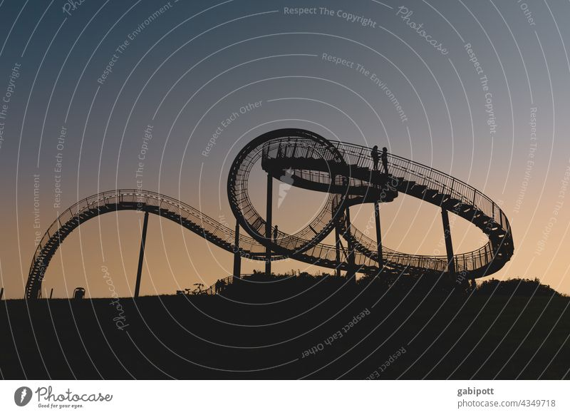 Turning loops (only for those who are free from giddiness) Roller coaster Leisure and hobbies Multicoloured Exterior shot Sky Blue Copy Space top Joy Sun Sunset