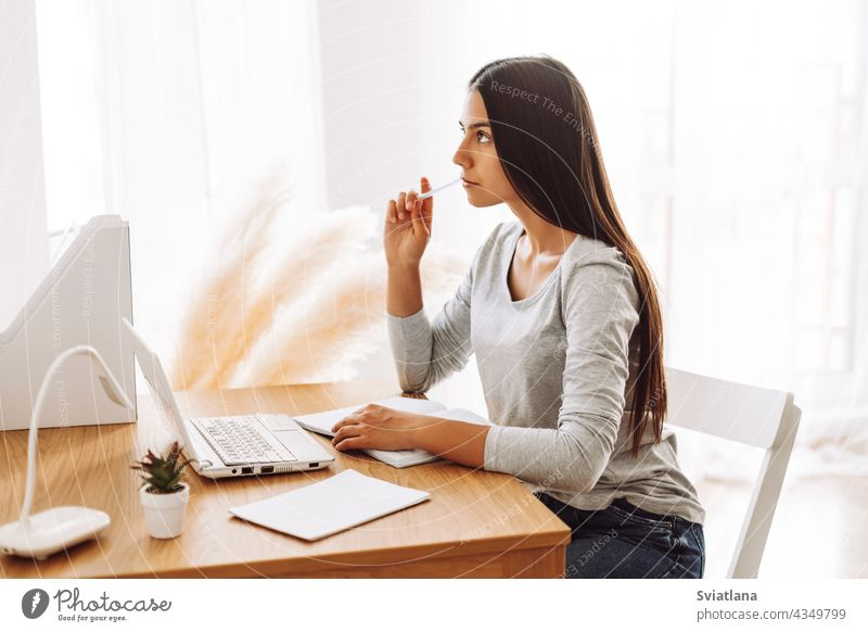 A student girl makes notes in a notebook, looks thoughtfully into the distance, uses a laptop. Modern technologies, online education, training sitting desk