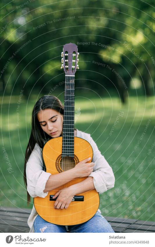 An attractive girl with a guitar in the park. The concept of creative hobbies and professionals. The girl is a musician portrait guitarist lifestyle female