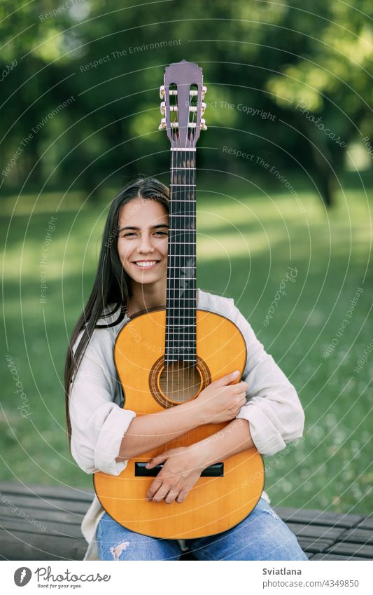 Portrait of a young girl guitarist who smiles and holds a guitar in her hands. Girl-musician, music, hobby park portrait creative lifestyle female woman