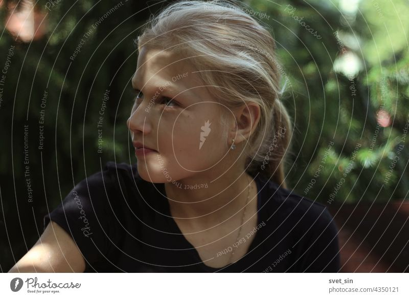 A blond teenage girl in a black T-shirt is sitting outdoors in the greenery and looks away with interest. Portrait of a pretty blonde girl in a semi-profile with sun glare on her face.