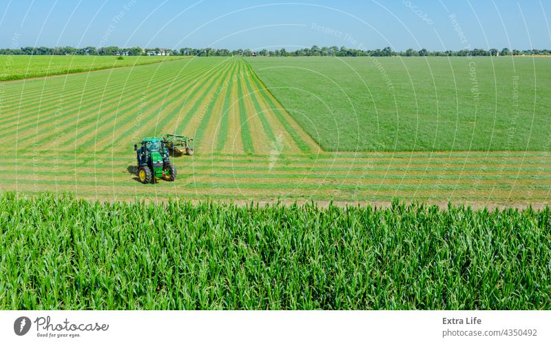 Aerial view of tractor as tow lawn mower machinery behind Above Agriculture Alfalfa Attached Clipper Clover Crop Cut Cutter Drag Farming Farmland Field Grass