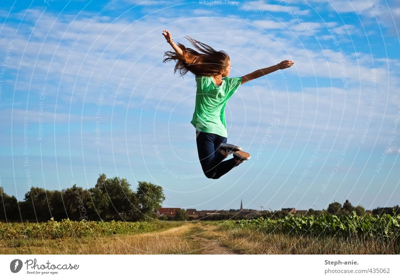 up Feminine Young woman Youth (Young adults) 1 Human being Earth Sky Clouds Summer Beautiful weather Grass Field T-shirt Jeans Long-haired To enjoy Jump Free