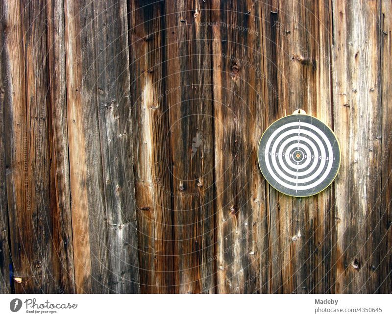 Round dartboard for playing darts on the brown wood of the facade of an old barn on a farm in Rudersau near Rottenbuch in the district of Weilheim-Schongau in Upper Bavaria