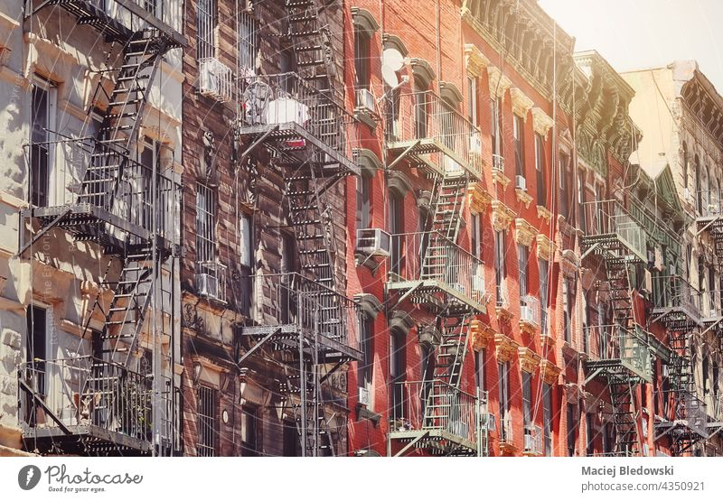 Old buildings with fire escapes in New York City, color toning applied, USA. NYC townhouse city old Manhattan retro vintage stairs apartment urban architecture