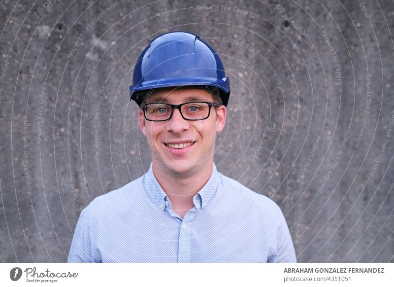 portrait of a smiling man wearing a hard hat on a concrete wall background mid white engineer call outdoor day architect smile helmet head shot working industry