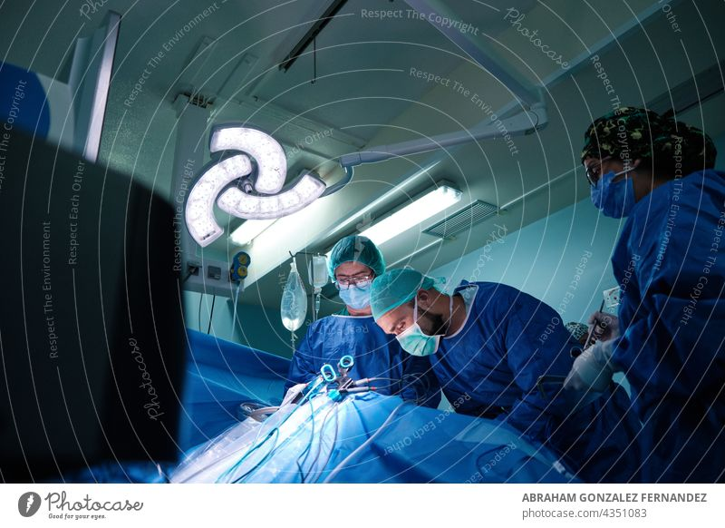 surgeons operating in an operating room using the laparoscopy technique man woman three mid adult nurse operation surgery indoor hospital blue uniform sterile
