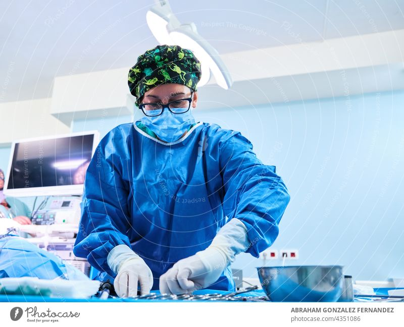 nurse prepares surgical material on a sterile table in the operating room woman adult scissor surgeon doctor operate mask hospital surgery medicine care