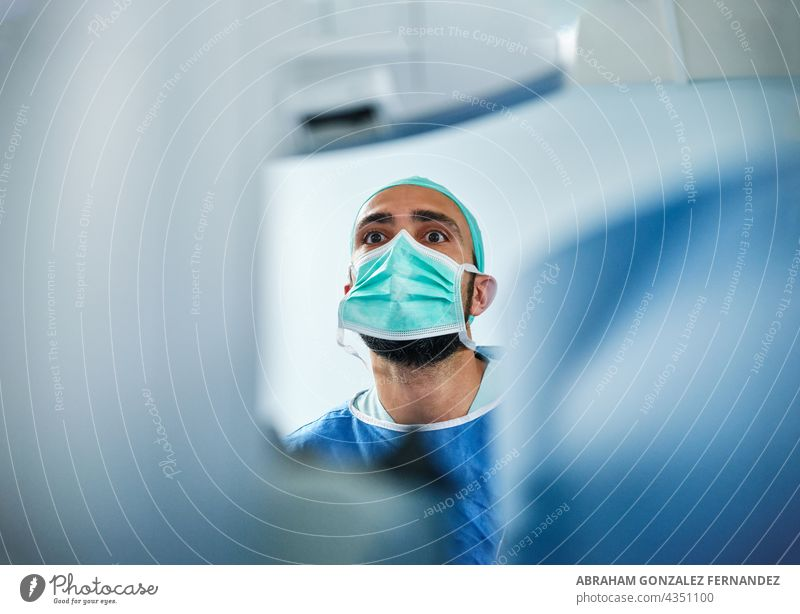 focused doctor watches a monitor during a surgical procedure at a hospital man adult white surgeon face mask indoor operation room blue technology medical