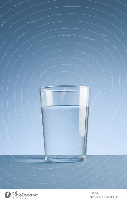 Minimalist photo of glass of clean drinking water on blue background Water Glass Clean Clear Drinking water Minimalistic Beverage Liquid Transparent Blue Purity