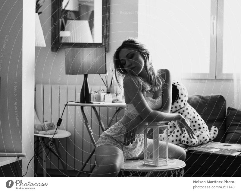 Black and white portrait of a beautiful caucasian woman in the livingroom blonde Caucasian lifestyles Black & white photo confident fashion Blonde