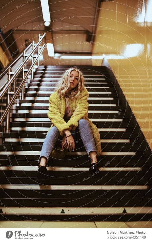 Portrait of a blonde caucasian woman on the stairs of a train station fashion lifestyle casual coat yellow Lifestyle Woman Style young attractive indoors
