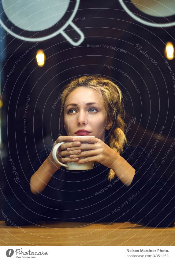 Portrait of a blonde woman holding a cup of coffee Cafeteria hot Hot drink Blonde Caucasian thoughtful lifestyle Beverage coffee shop mood cool moody Breakfast
