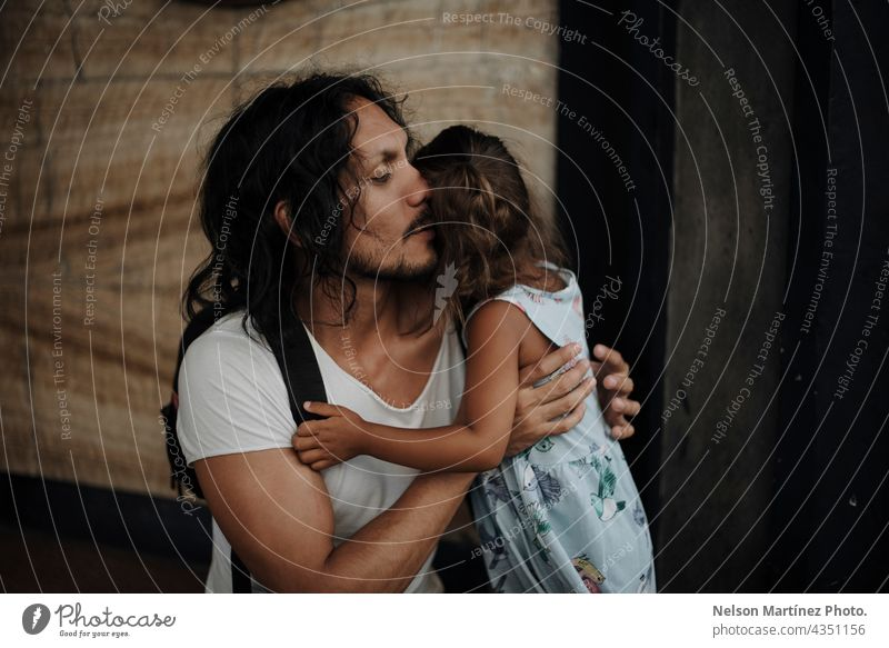 Father with long black hair hugging his daughter hispanic latin portrait family father dad childhood girl female long hair together love parent man lifestyle