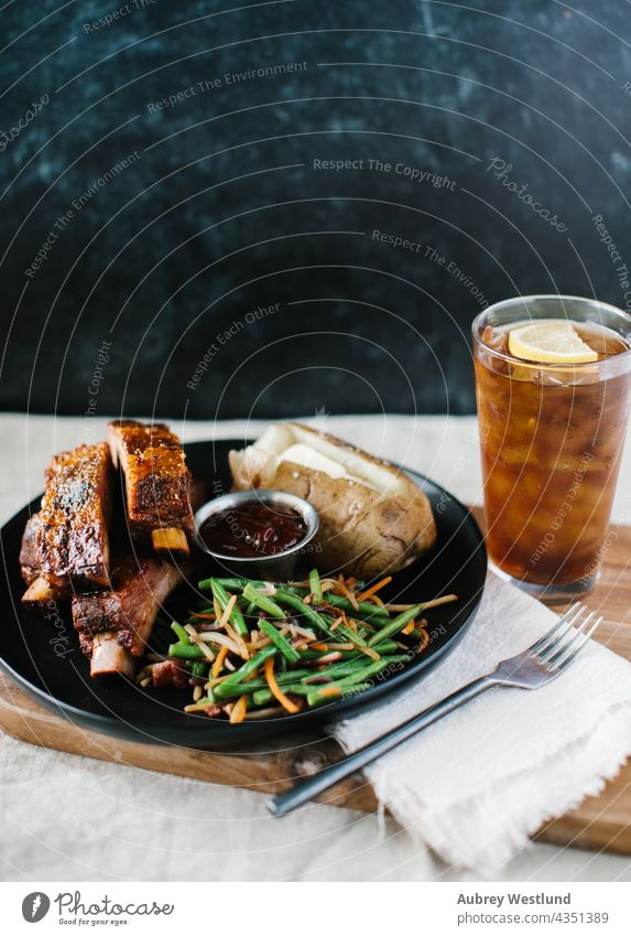 Ribs dinner meal with fancy green beans and potato with a modern black backdrop american background baked baked potato barbecue barbecued barbeque bbq beef