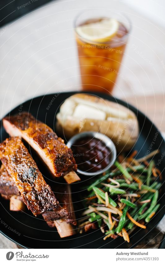 Ribs dinner meal with fancy green beans and potato on a farmhouse country linen tablecloth american background baked baked potato barbecue barbecued barbeque
