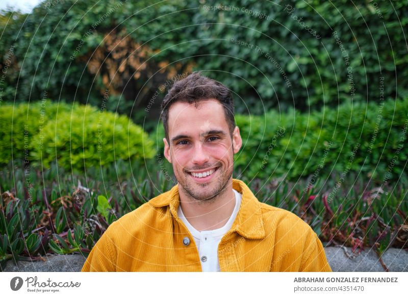 portrait of a smiling young man in a yellow shirt against a background of green bushes mid white smile beard bushy natural plant outdoor day happy people