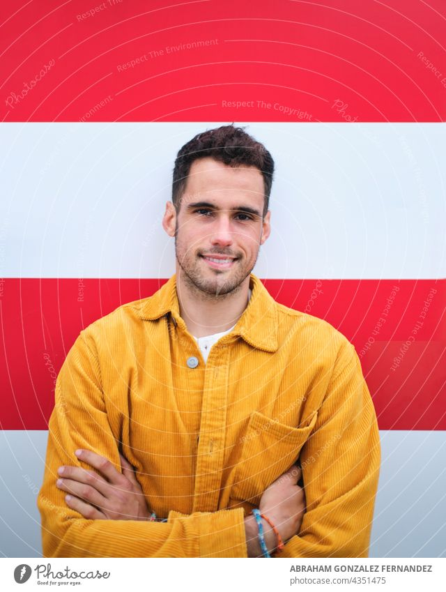 portrait of a young man in yellow corduroy shirt on a white and red striped background mid one smile arm fold wall outdoor day vertical headshot beard brunette